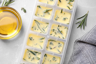 Ice cube tray with herbs frozen in oil and fresh rosemary on grey table, flat lay