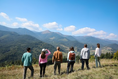 Group of people spending time together in mountains, back view