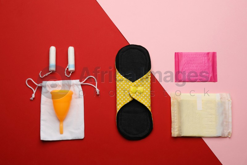 Cloth menstrual pad near other reusable and disposable female hygiene products on color background, flat lay