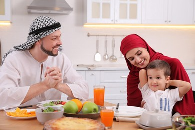 Happy Muslim family eating together at table in kitchen