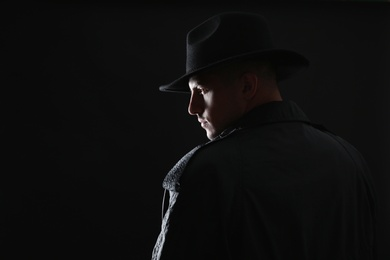Old fashioned detective in hat on dark background. Space for text