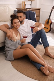 Lovely couple with glasses of wine enjoying time together at home