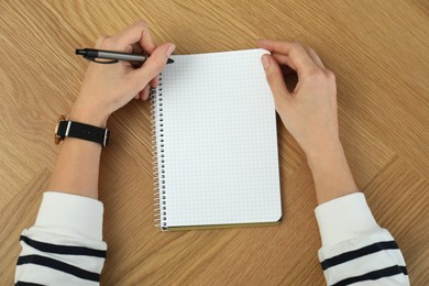 Left-handed woman writing in notebook at wooden table, top view
