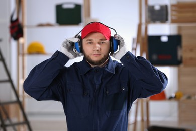 Worker wearing safety headphones indoors. Hearing protection device