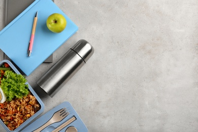 Flat lay composition with thermos and food on light grey table. Space for text