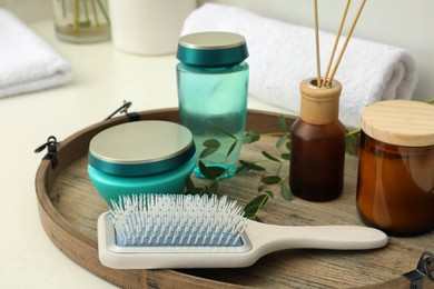 Hair care cosmetic products and brush on table indoors