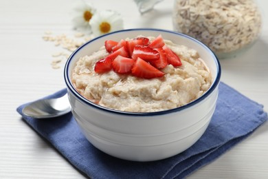 Tasty oatmeal porridge with strawberries served on white wooden table