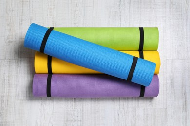 Bright rolled camping mats on white wooden background, flat lay