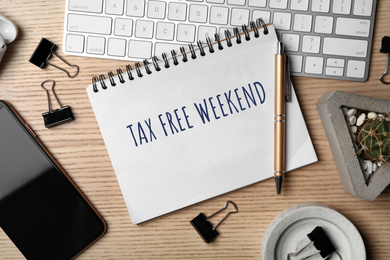 Notebook with text TAX FREE WEEKEND, keyboard and smartphone on wooden table, flat lay