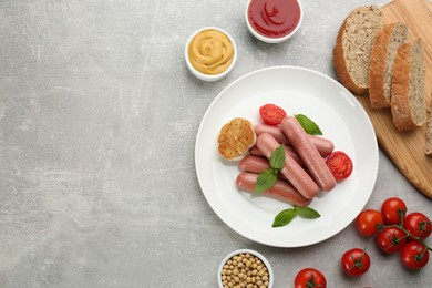 Flat lay composition with vegetarian sausages and vegetables on grey table. Space for text
