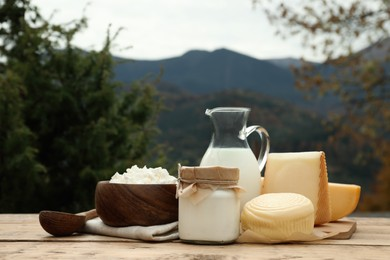 Tasty cottage cheese and other fresh dairy products on wooden table in mountains