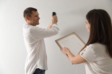 Couple decorating room with picture together. Interior design