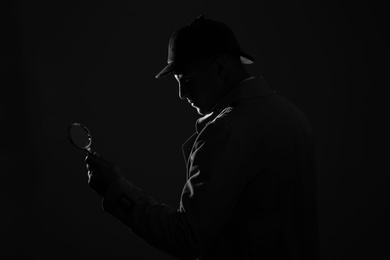Old fashioned detective with magnifying glass on dark background, black and white effect