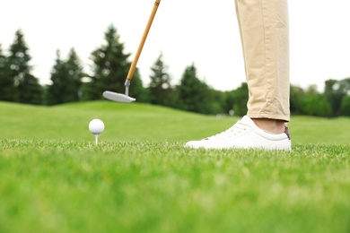 Man playing golf on green course. Sport and leisure