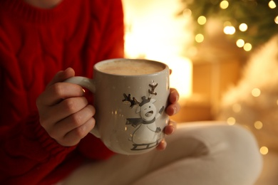 Woman with cup of drink and blurred Christmas lights on background, closeup