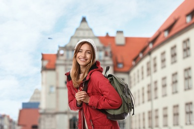 Happy traveler with backpack in foreign city during vacation