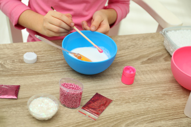 Little girl making homemade slime toy at table, closeup