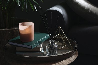 Wooden tray with decorations and books on table in room