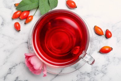 Fresh rose hip tea and berries on white marble table, flat lay