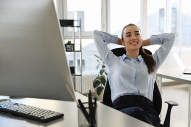 Young businesswoman relaxing in office chair at workplace