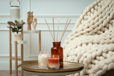 Air reed freshener and burning candles on table indoors. Interior elements