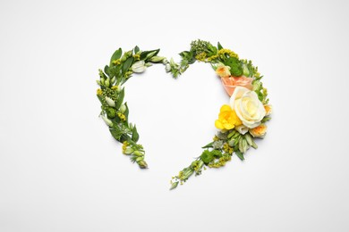 Beautiful heart shaped floral composition on light background, flat lay