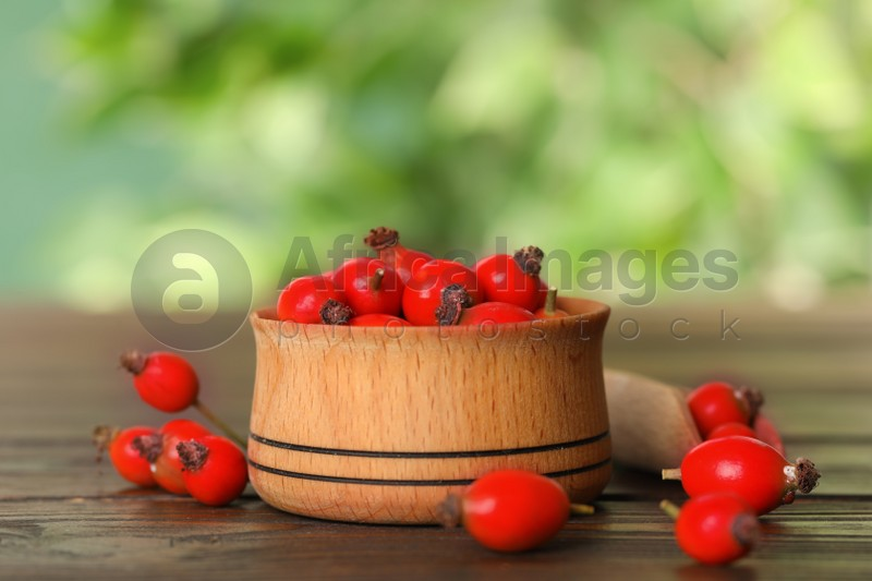 Ripe rose hip berries with bowl on wooden table