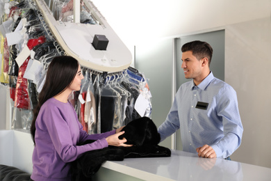 Worker receiving fur coat from client at dry-cleaner's