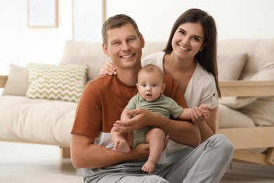 Portrait of happy family with their cute baby at home