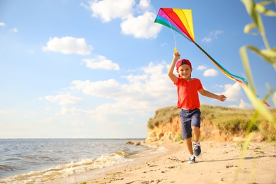 Cute little child with kite running on beach near sea. Spending time in nature