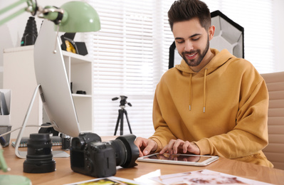 Professional photographer working at table in office
