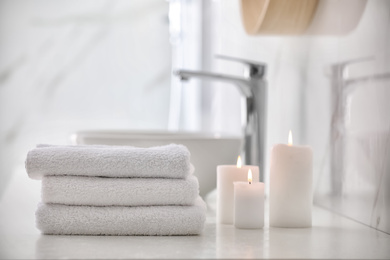 Stack of fresh towels and burning candles on countertop in bathroom