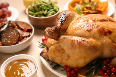 Traditional Thanksgiving day feast with delicious cooked turkey and other seasonal dishes served on wooden table, closeup