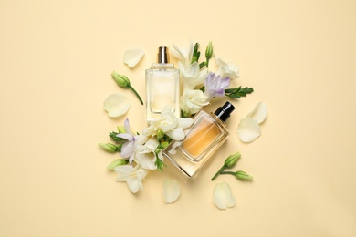 Flat lay composition with different perfume bottles and freesia flowers on yellow background