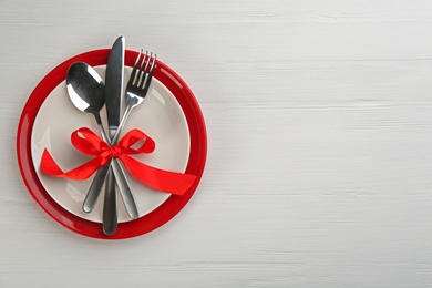 Beautiful table setting on white wooden background, top view with space for text. Valentine's Day dinner