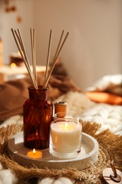 Air reed freshener and burning candles on bed indoors. Interior elements