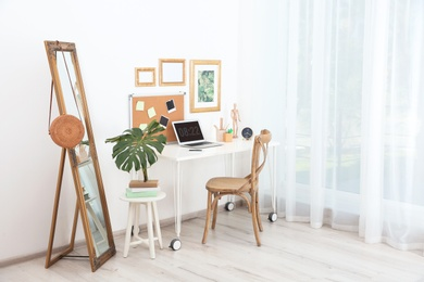 Stylish workplace with laptop on table in room