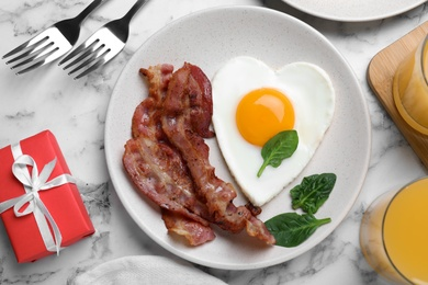 Romantic breakfast with fried bacon and heart shaped egg on white marble table, flat lay. Valentine's day celebration