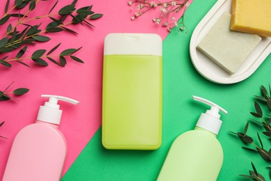 Flat lay composition with shower gel bottles and green leaves on color background