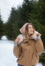 Young woman in snowy conifer forest. Winter vacation