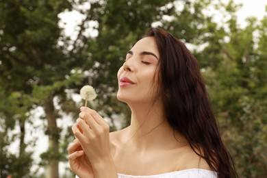 Beautiful young woman blowing dandelion in park. Allergy free concept