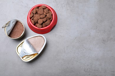 Wet and dry pet food on grey table, flat lay. Space for text
