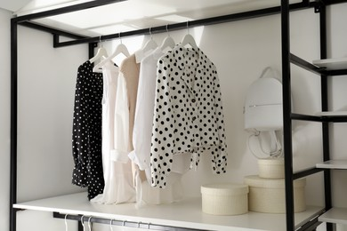 Storage rack with stylish women's clothes and accessories indoors
