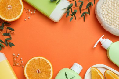 Flat lay composition with shower gel bottles and leaves on orange background, space or text