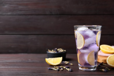 Organic blue Anchan with lemon in glass on wooden table, space for text. Herbal tea