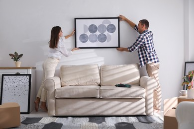 Happy couple hanging picture on white wall together. Interior design