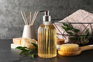Stylish dispenser with liquid soap and other bathroom amenities on dark table