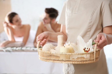 Massage therapist with spa essentials and young couple in wellness center