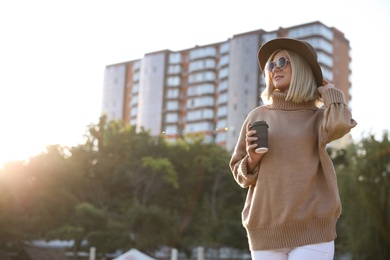 Woman in stylish sweater with cup of coffee on city street