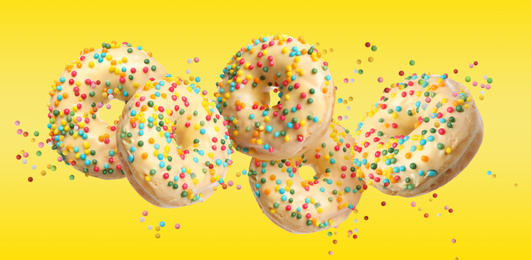 Set of falling delicious donuts on yellow background. Banner design